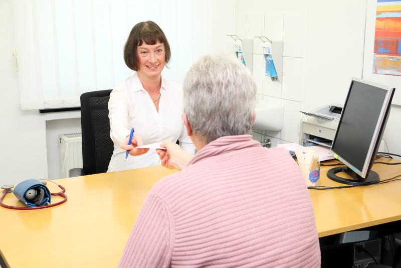 Das Foto zeigt Frau Dr. Duplois im Sprechzimmer mit einer Patientin, sie reicht ihr ein Rezept.