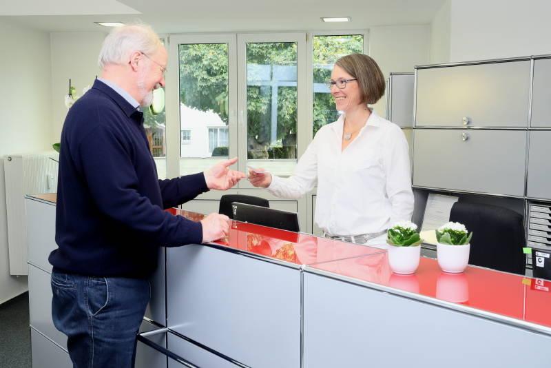 Das Foto zeigt Frau Dr. Nave an der Anmeldung mit einem Patienten, sie reicht ihm ein Rezept.