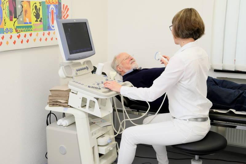 Das Foto zeigt Frau Dr. Nave bei der Ultraschalluntersuchung eines Patienten.