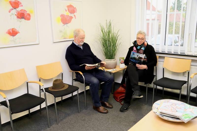 Das Foto zeigt ein freundlich eingerichtetes Wartezimmer mit Blumenbildern, einer Graspflanze und zwei Patienten.